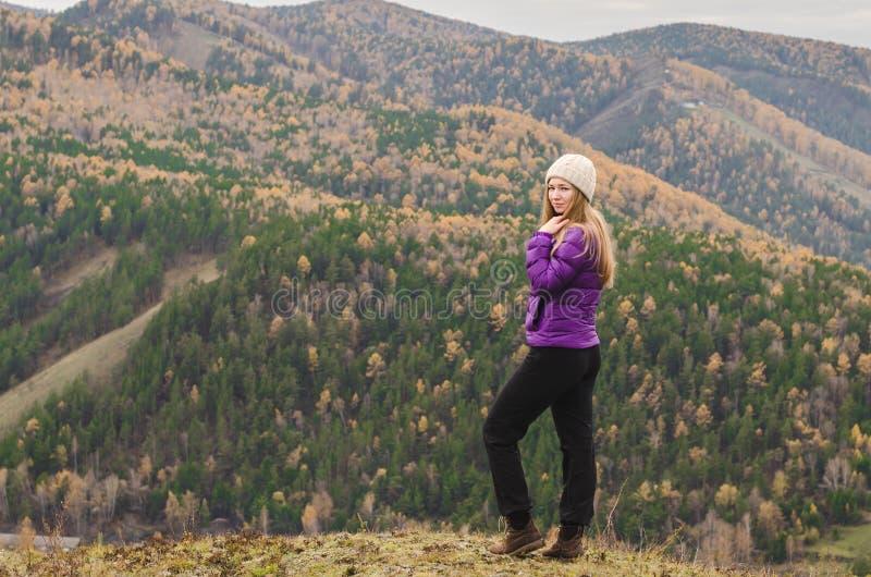 Una muchacha en una chaqueta de la lila mira hacia fuera en la distancia en una montaña, una vista de las montañas y un bosque ot imágenes de archivo libres de regalías