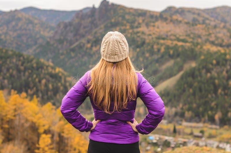 Una muchacha en una chaqueta de la lila mira hacia fuera en la distancia en una montaña, una vista de las montañas y un bosque ot foto de archivo