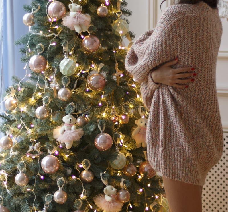 Una muchacha en costes rosados de un suéter del punto sobre un árbol del Año Nuevo para adornar un árbol de navidad, para prepara fotografía de archivo libre de regalías