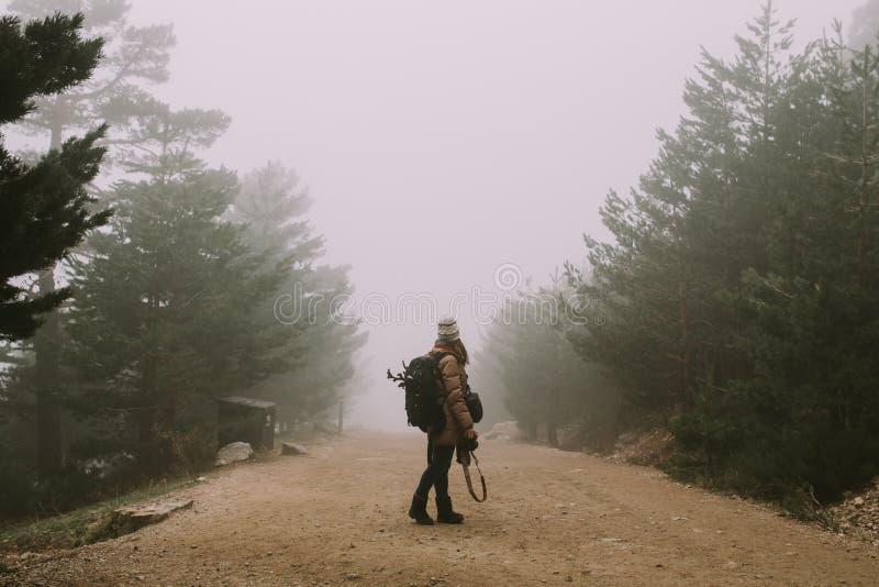 Una muchacha en el medio de un camino este para el mirar hacia la niebla gruesa foto de archivo libre de regalías