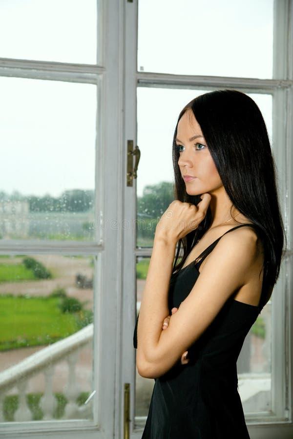Una muchacha en el travesaño de la ventana imagen de archivo