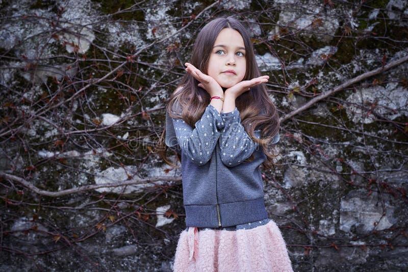 Una muchacha en falda rosada y chaqueta gris imagenes de archivo