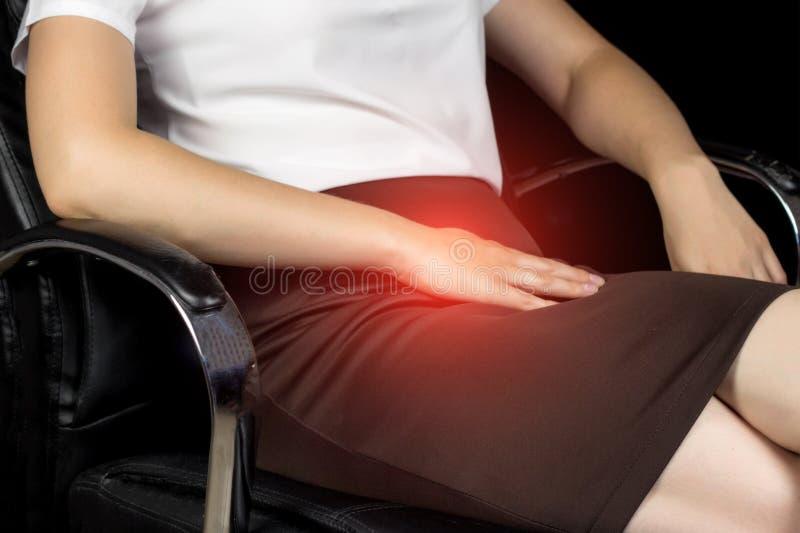 Una muchacha en una falda se sienta en una silla y los aferrar al área de la ingle, dolor en el abdomen más bajo, infección sexua foto de archivo libre de regalías