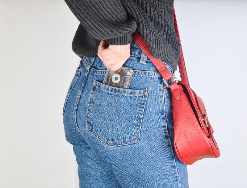 Una muchacha en a imita los vaqueros aptos, un suéter y con un bolso rojo en el borde saca un casete audio retro de su bolsillo imagenes de archivo