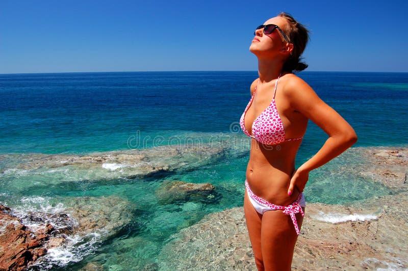 Una muchacha en la playa rocosa fotos de archivo
