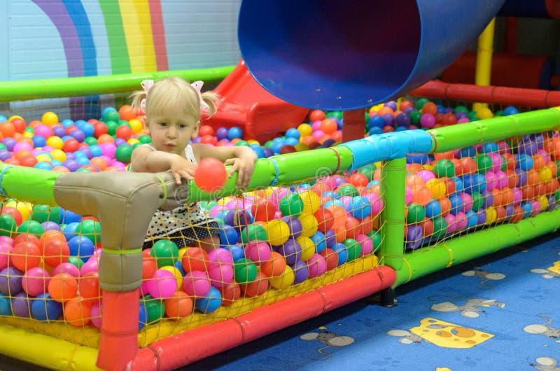Una muchacha en la sala de juegos, donde hay muchas bolas coloreadas fotos de archivo libres de regalías