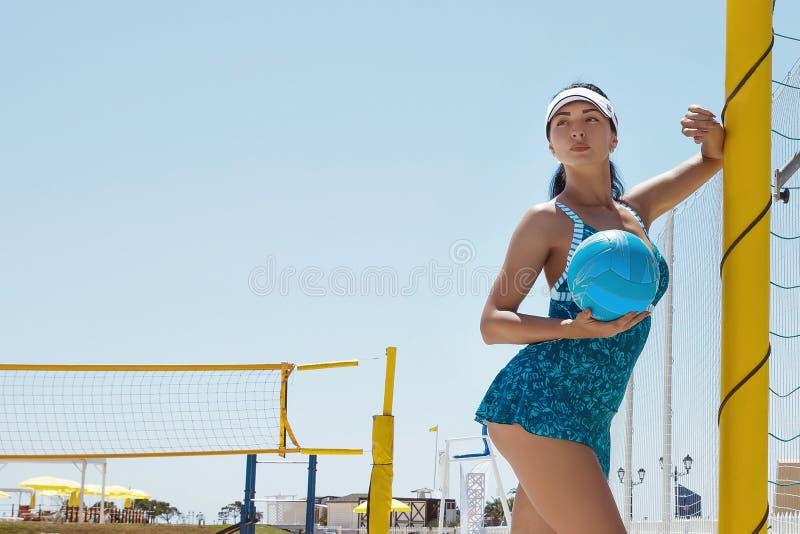Una muchacha en los deportes azules se viste con una bola del voleibol fotografía de archivo