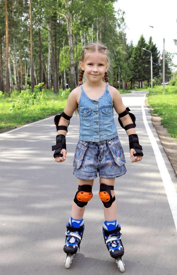 Una muchacha en pcteres de ruedas fotografía de archivo