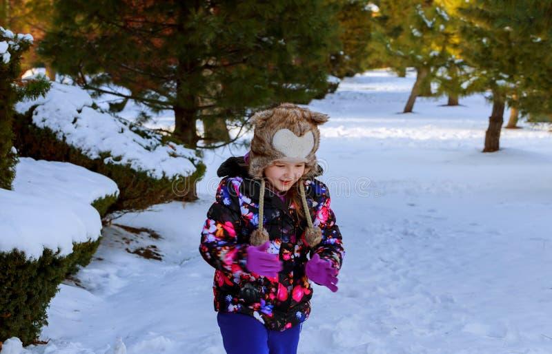 Una muchacha en ropa del invierno corre a una colina de la nieve con jugar en invierno con nieve foto de archivo
