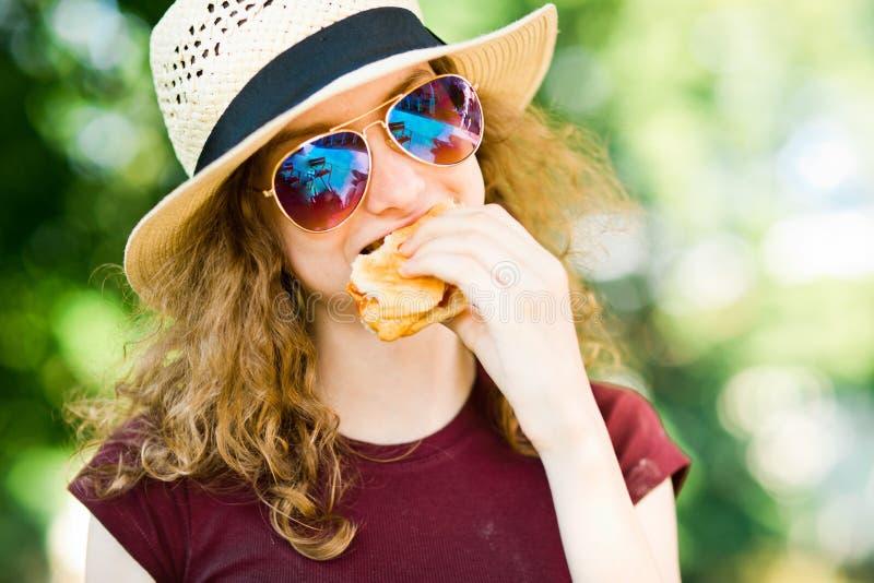 Una muchacha en sombrero con la hamburguesa de los vidrios de sol arrancada con los dientes fotografía de archivo