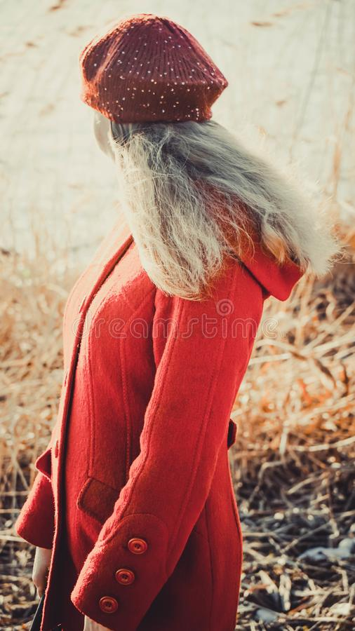 Una muchacha en soportes rojos de la ropa del otoño con su parte posterior contra la perspectiva de la naturaleza imagenes de archivo