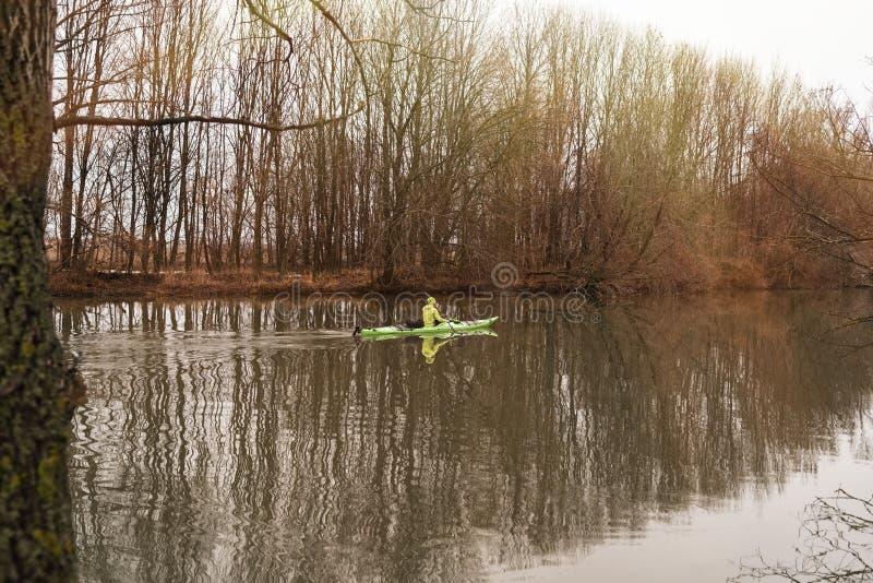 Una muchacha en un kajak Los flotadores de la muchacha en el río en un kajak foto de archivo