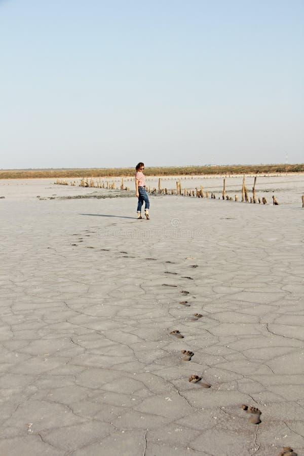 Una muchacha en un lago con fango negro curativo foto de archivo libre de regalías