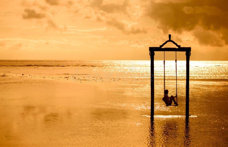 Una muchacha en un oscilación sobre el mar en la puesta del sol en Bali, Indonesia fotos de archivo libres de regalías