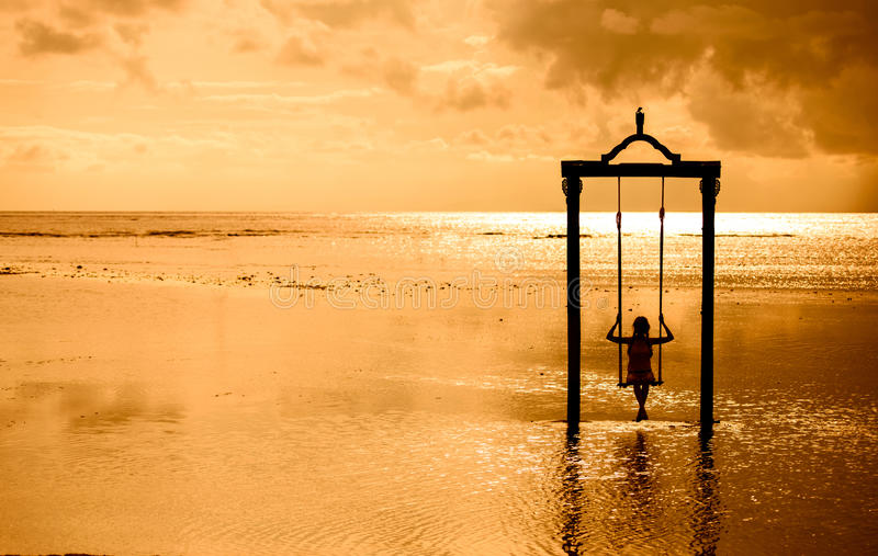 Una muchacha en un oscilación sobre el mar en la puesta del sol en Bali, Indonesia 2 fotos de archivo