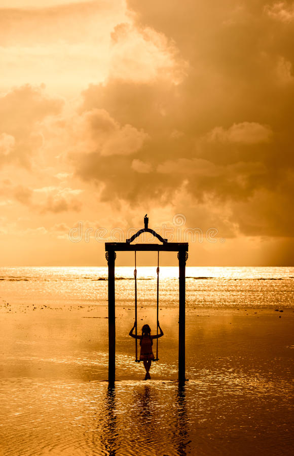 Una muchacha en un oscilación sobre el mar en la puesta del sol en Bali, Indonesia 3 foto de archivo