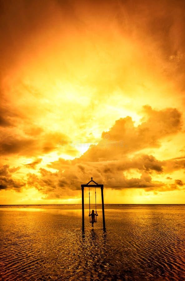 Una muchacha en un oscilación sobre el mar en la puesta del sol en Bali, Indonesia 4 fotos de archivo libres de regalías