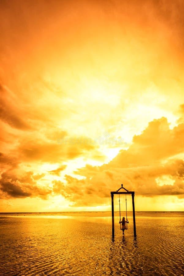 Una muchacha en un oscilación sobre el mar en la puesta del sol en Bali, Indonesia 5 imágenes de archivo libres de regalías