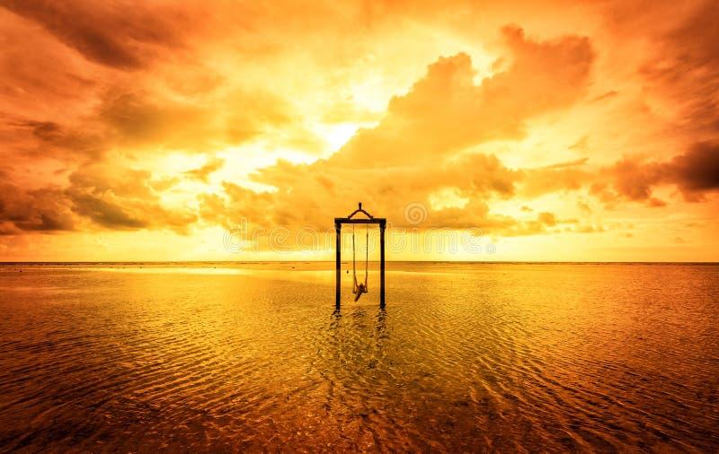 Una muchacha en un oscilación sobre el mar en la puesta del sol en Bali, Indonesia 6 fotos de archivo
