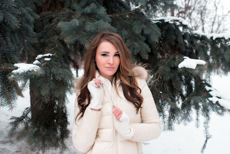 Una muchacha en un parque del invierno en un fondo de árboles verdes, en una chaqueta blanca del plumón con el pelo marrón largo, foto de archivo libre de regalías