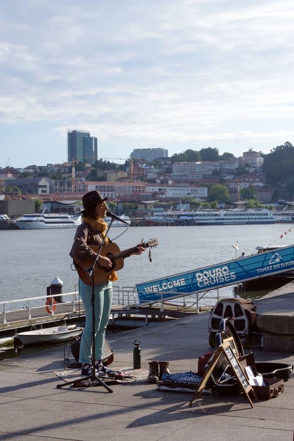 Una muchacha en un sombrero con una guitarra canta canciones líricas en el terraplén del río del Duero en la ciudad de Oporto imagenes de archivo