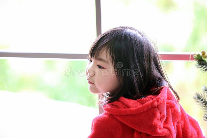 Una muchacha en un traje rojo que hace una pausa la ventana Soportes de la muchacha cerca de la ventana que mira a un lado niño s imagen de archivo libre de regalías