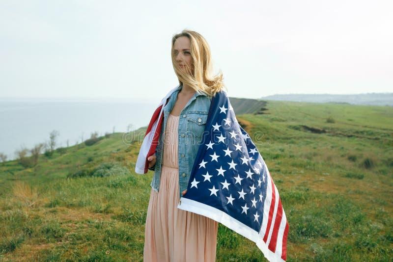 Una muchacha en un vestido coralino y una chaqueta del dril de algod?n sostiene la bandera de los Estados Unidos en sus manos 4 d fotografía de archivo