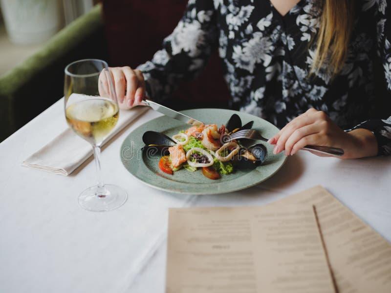 Una muchacha en un vestido hermoso está comiendo un plato delicioso de los mariscos en un restaurante hermoso Tiempo perfecto, co imagenes de archivo