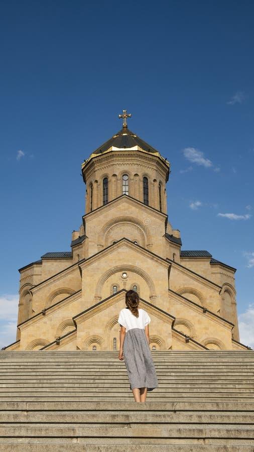 Una muchacha en un vestido largo se coloca en el fondo de un templo cristiano viejo fotos de archivo