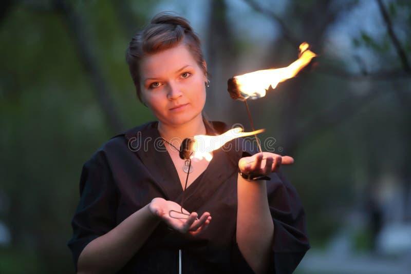 Una muchacha en un vestido negro muestra una demostración del fuego fotos de archivo libres de regalías