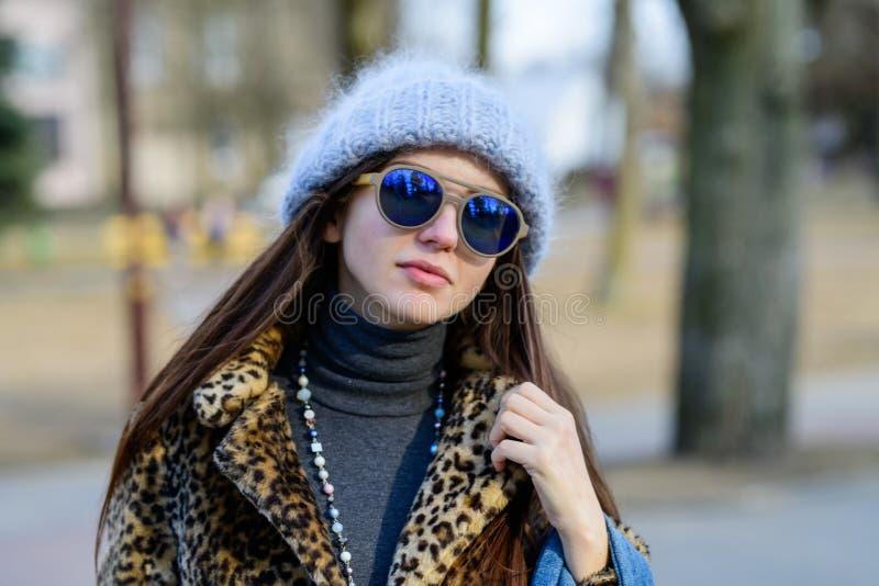 Una muchacha en vidrios azules y un sombrero gris regordete caliente que presenta afuera en la estación fría Retrato de una mucha imagen de archivo libre de regalías