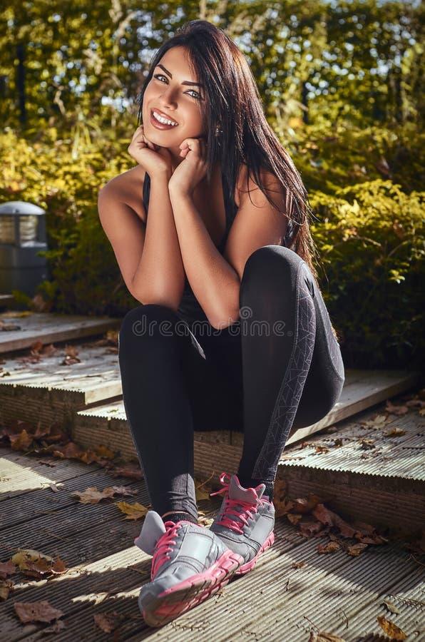 Una muchacha encantadora de la aptitud con la ropa de deportes que lleva bronceada de la piel que se sienta en pasos de madera en imagenes de archivo