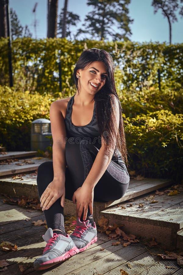Una muchacha encantadora de la aptitud con la ropa de deportes que lleva bronceada de la piel que se sienta en pasos de madera en imágenes de archivo libres de regalías