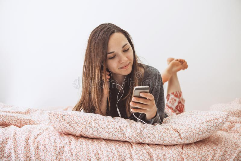 Una muchacha escucha la música o hecho un podcast fotos de archivo libres de regalías