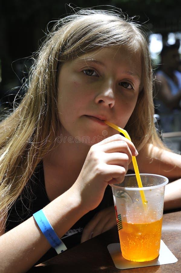 Una muchacha está bebiendo un cóctel fotos de archivo