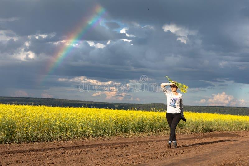 Una muchacha está caminando a lo largo de un camino rural a través de un campo amarillo floreciente D?a de verano asoleado fotografía de archivo libre de regalías