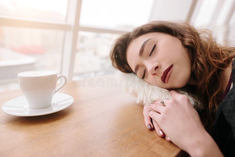 Una muchacha está durmiendo en un cuaderno en un café imagenes de archivo