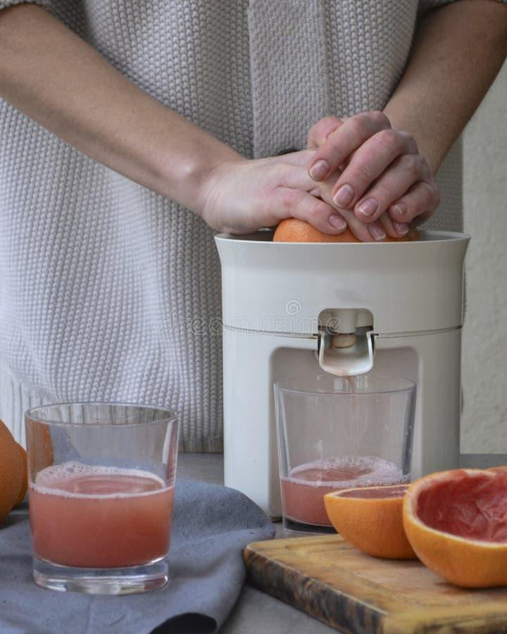 Una muchacha está haciendo el jugo de pomelo fresco fotos de archivo