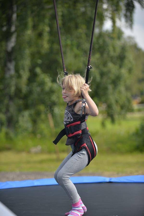 Una muchacha está haciendo el salto en la atracción de salto fotografía de archivo