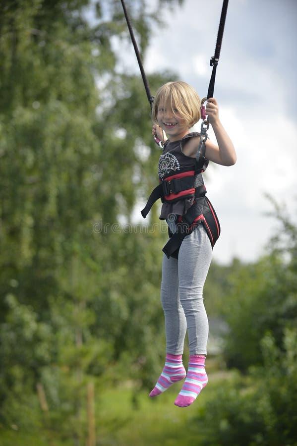 Una muchacha está haciendo el salto en la atracción de salto fotos de archivo