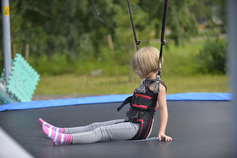 Una muchacha está haciendo el salto en la atracción de salto imágenes de archivo libres de regalías