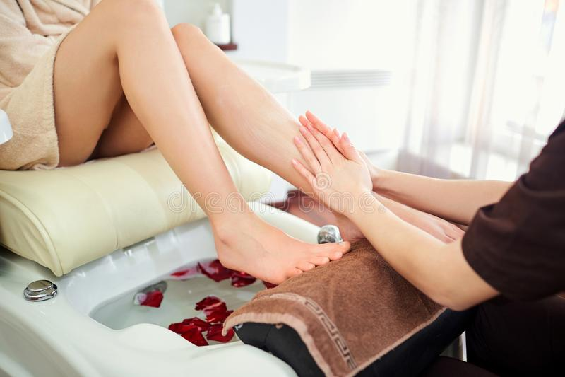 Una muchacha está haciendo un masaje del pie en un salón de la pedicura que se sienta en a imagen de archivo libre de regalías