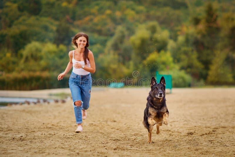 Una muchacha está jugando con su perro en la playa en parque del verano fotografía de archivo