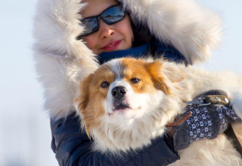 Una muchacha está sosteniendo un perro en sus brazos en invierno foto de archivo libre de regalías