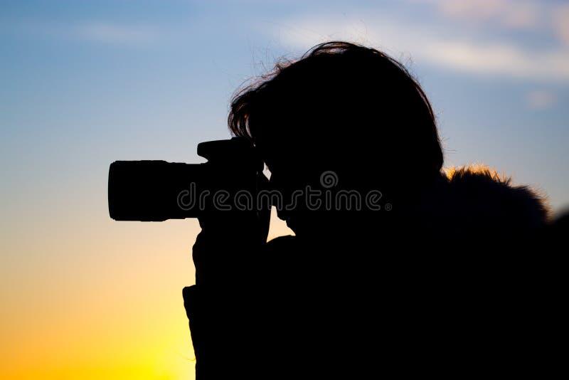 Una muchacha está tomando imágenes con una cámara en la puesta del sol fotografía de archivo libre de regalías
