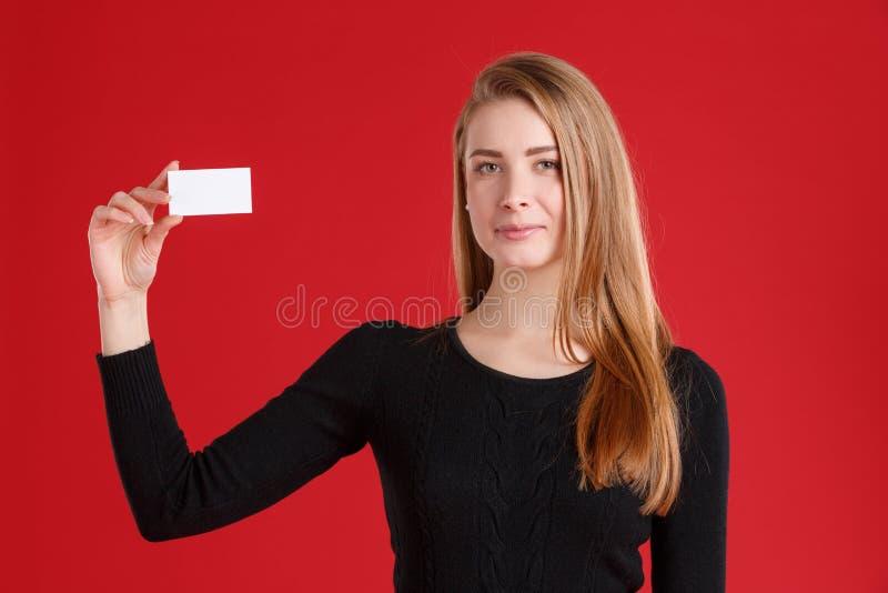 Una muchacha europea joven, sosteniendo una tarjeta de visita vacía en una mano foto de archivo libre de regalías