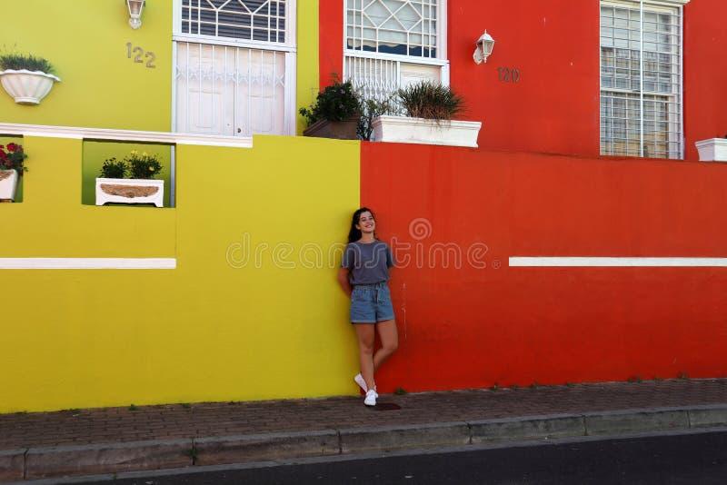 una muchacha feliz adorable tomar una foto contra la pared colorida, en calle del cuarto de BO Kaap, Cape Town imágenes de archivo libres de regalías