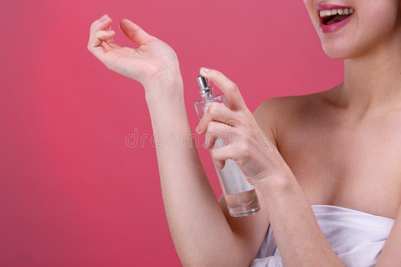 Una muchacha feliz aplica perfume al área de la muñeca y sonríe lindo En un fondo rosado Primer fotos de archivo