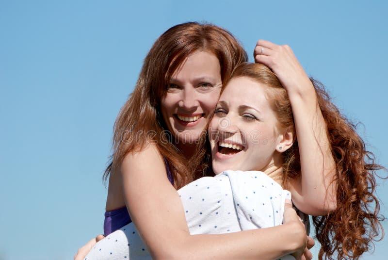 Una muchacha feliz joven con la madre imagen de archivo