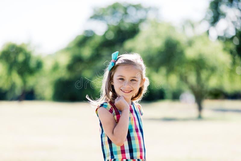 Una muchacha feliz joven en el vestido a cuadros colorido que se coloca en el parque, foto de archivo libre de regalías